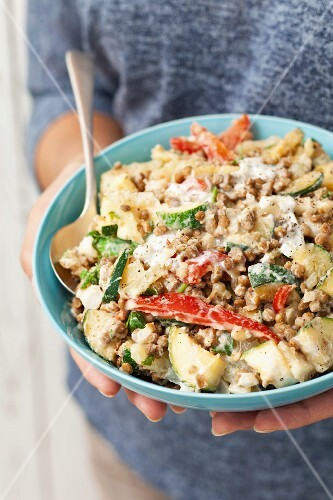 A woman holding a bowl of potato salad with lentils, peppers, courgettes and a yoghurt dressing