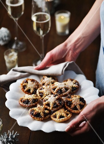 A woman serving a plate of mince pies for Christmas