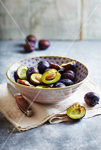 Fresh plums in a ceramic bowl