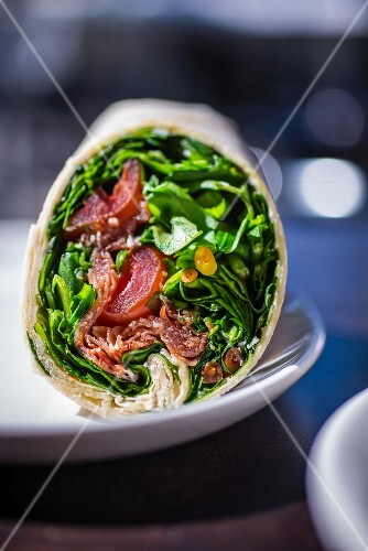 A wrap with lettuce, sausage and tomatoes
