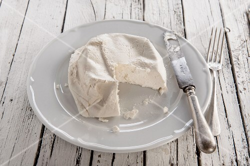 Ricotta on a white plate with a knife