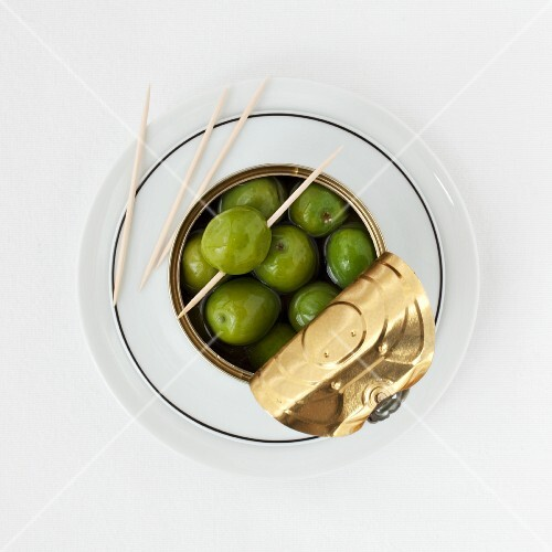 A tin of green olives and cocktail sticks