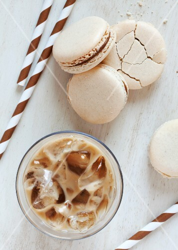 A glass of iced coffee served with coffee macaroons