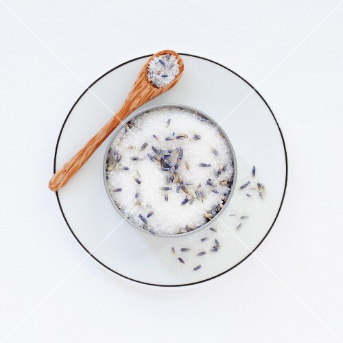 A pot of lavender sugar on a saucer with a spoon
