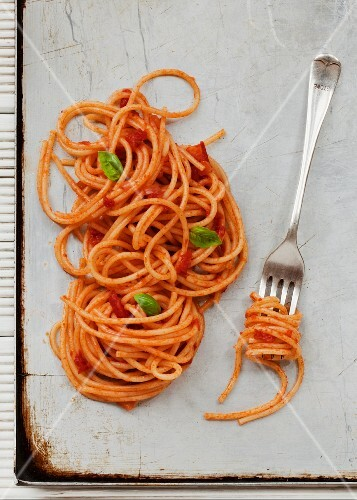Spaghetti with tomato sauce on a baking tray