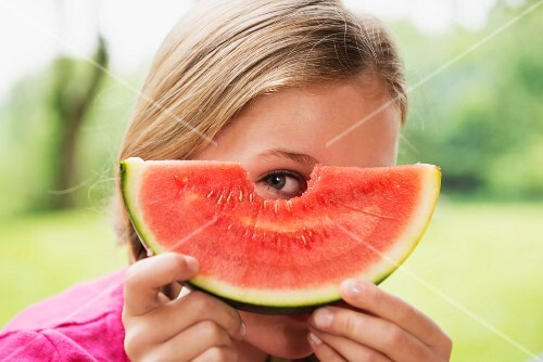 A girl looking through a hole in a watermelon slice