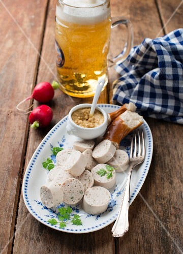White sausage with mustard, pretzel, radishes and beer