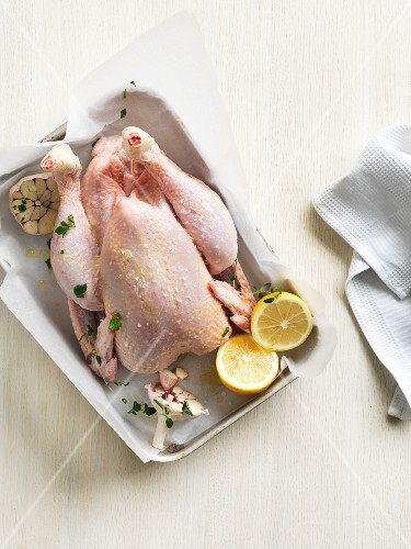 Chicken with garlic, lemons and herbs on a baking tray
