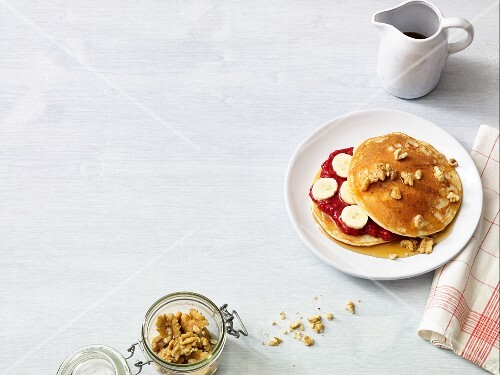 Almond pancakes with jam, bananas, maple syrup and walnuts