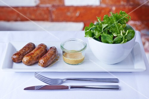 Game sausages with herb salad