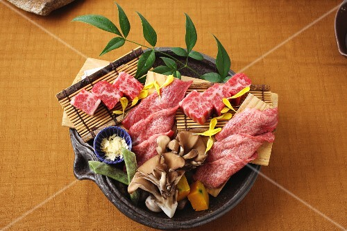 Raw wagyu beef on a bamboo mat with oyster mushrooms (Japan)
