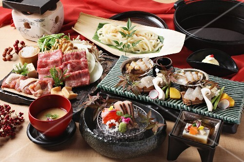 Japanese party dishes with beef, udon noodles and sashimi (Japan)