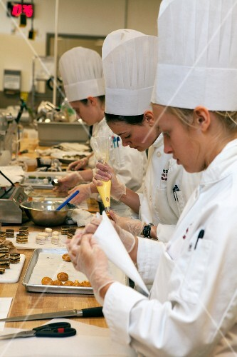 Young chefs making eclairs and petit fours