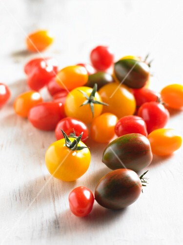 Various tomatoes on a white wooden surface