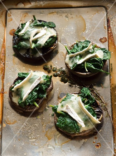 Four baked mushrooms with spinach and Camembert on a baking tray
