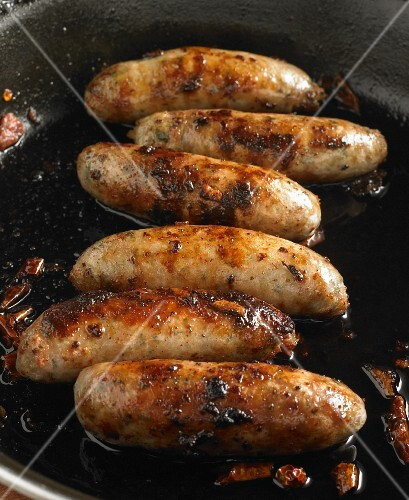 Six sausages frying in a pan