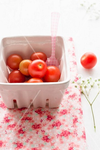 Cherry tomatoes in a cardboard punnet with a plastic fork