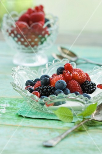 Yogurt with fresh fruit (strawberry, redcurrants, blackberries, raspberries and blueberries) in a glass bowl