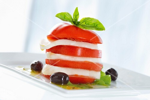 A tomato and mozzarella tower with basil and olives