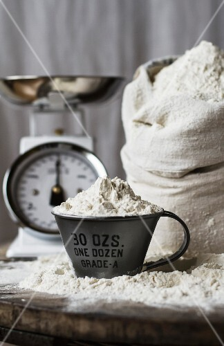 A measuring jug of flour in front of a sack of flour and a pair of kitchen scales