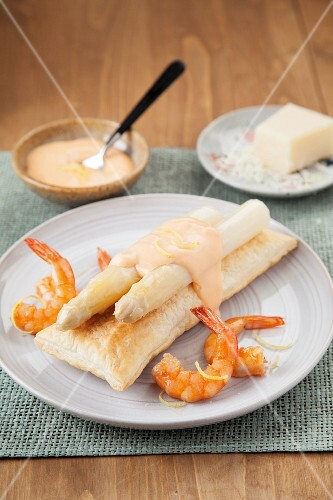 White asparagus on puff pastry with shrimps and a creamy cheese sauce