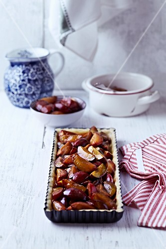 Shortcrust pastry with caramelised plums in a cake tin