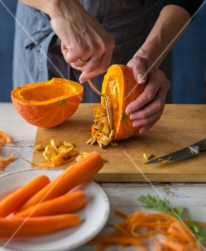 Oven roasted vegetables being made: a pumpkin being deseeded