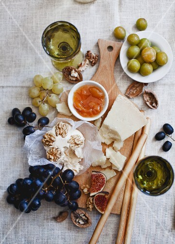 A cheese platter with grapes, figs, nuts, chutney, grissini and wine