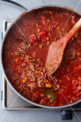 Minced meat sauce with vegetables for lasagne in a pot on the hob