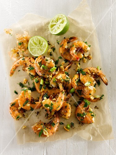 Lime and herb prawns with spring onions, peanuts, parsley, garlic and cracked pepper on parchment paper