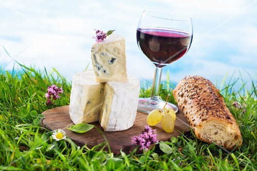 An arrangement of cheeses featuring blue cheese and red wine