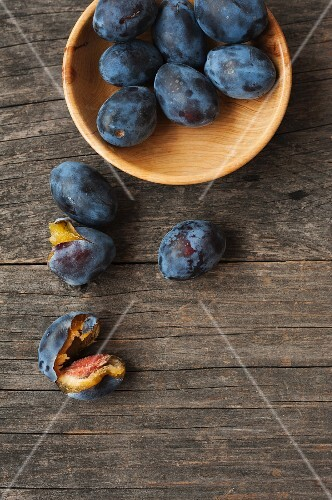 Fresh plums in a wooden bowl and next to it