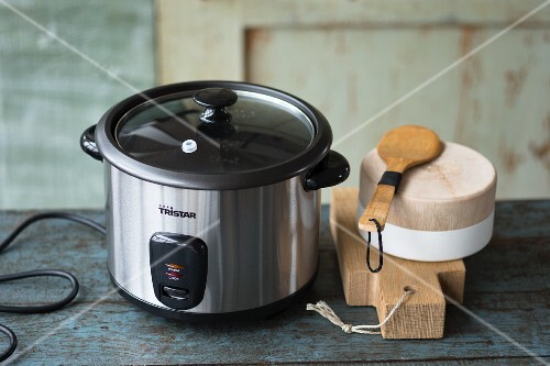 An electric rice cooker and wooden kitchen utensils