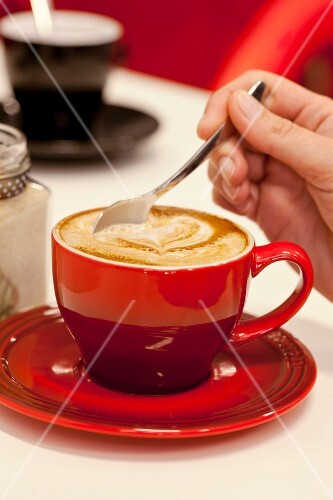 A hand stirring a hot cappuccino decorated with a heart