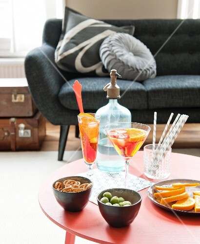 Cocktail glasses and bowl of snacks on red table