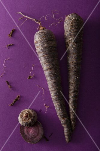 Black carrots on a purple surface