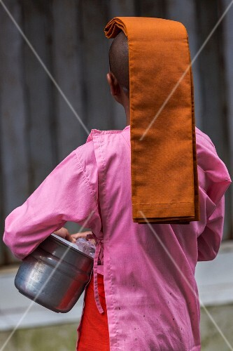 A young Buddhist nun collecting alms on a street in Yangon, Myanmar