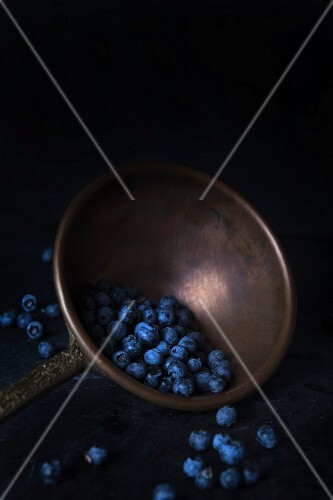 Blueberries in a pewter ladle on a black granite surface