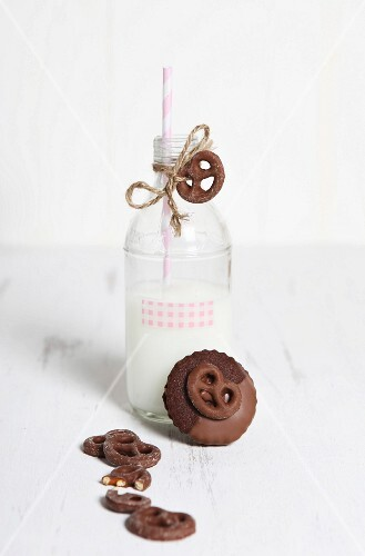 A bottle of milk with a straw and chocolate pretzels on a white wooden surface