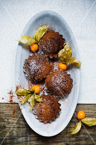 Mini chocolate cakes with physalis and icing sugar