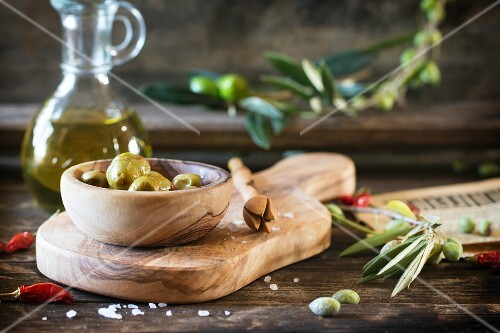 Green olives in an olive wood bowl and a bottle of olive oil on an old wooden table