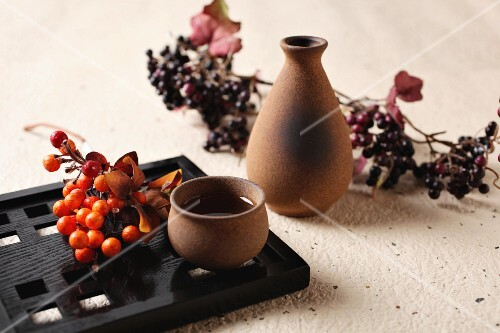Sake in a bowl and a carafe decorated with berries
