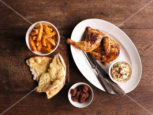 Grilled piri-piri chicken with side dishes and unleavened bread