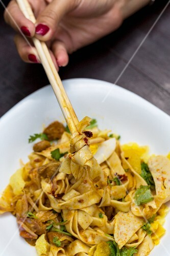 Burmese -tyle egg noodles being eaten with chopsticks