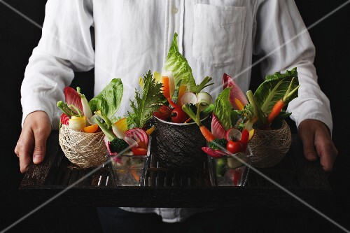 A man serving a tray of raw vegetables