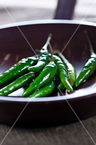 Green chilli peppers in a pan