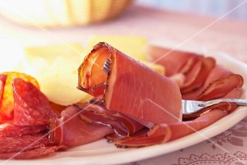 A supper plate with smoked ham, salami and cheese