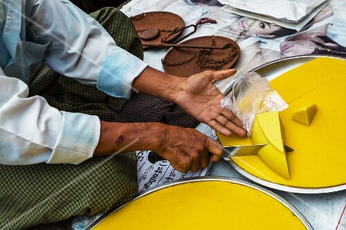 A man cutting chickpea tofu at a market in Yangon, Myanmar