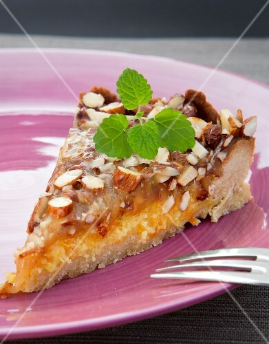 A slice of orange and almond tart garnished with lemon balm