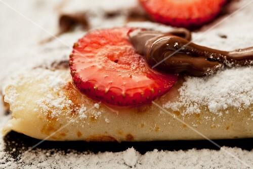 Crepes with chocolate sauce and strawberries (close up)